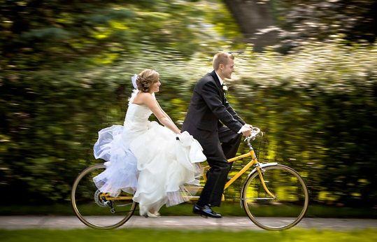 Фото свадебной фотосессии на велосипеде за городом.